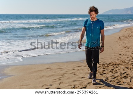 Male caucasian athlete walking along the seashore at sunny day while listening to music with headphones and resting after a long active run outdoors, copy space for text message to advertising content - stock photo