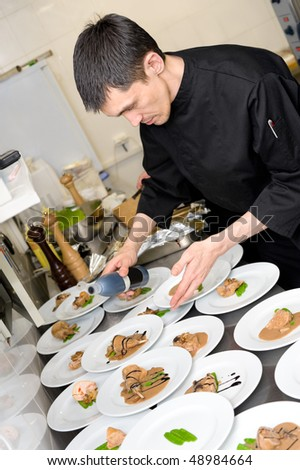 male caucasian chef in black uniform pours sauce on plates with lamb meat - stock photo