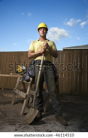 Male Caucasian construction worker in a yellow hardhat is holding a shovel while looking at the camera. Vertical shot. - stock photo
