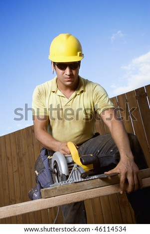 Male Caucasian construction worker in safety glasses and a hardhat cutting wood with a circular saw. Vertical shot. - stock photo