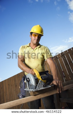 Male Caucasian construction worker in safety glasses and a hardhat. He is cutting wood with a circular saw. Vertical shot. - stock photo