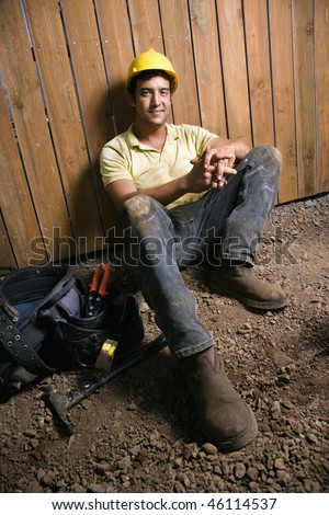 Male Caucasian construction worker sitting next to a tool bag.  He is wearing a yellow hardhat. Vertical shot.
