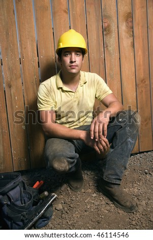 Male Caucasian construction worker squats next to a bag of tools while wearing a yellow hardhat. Vertical shot. - stock photo