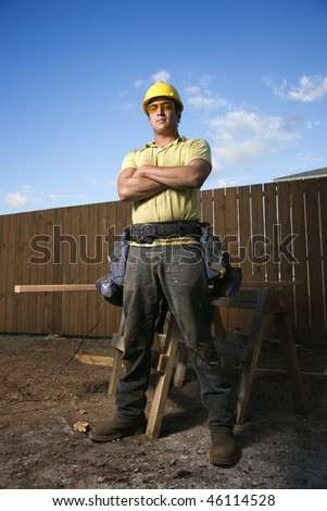 Male Caucasian construction worker stands confidently and looks into the camera. His arms are folded across his chest and a workbench can be seen behind him. Vertical shot. - stock photo