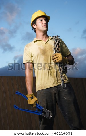 Male Caucasian construction worker wearing a yellow hardhat stands with heavy chain on his shoulder and bolt cutters in his hand. Vertical shot. - stock photo