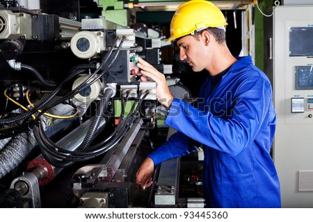 male caucasian operator operating industrial printing press - stock photo