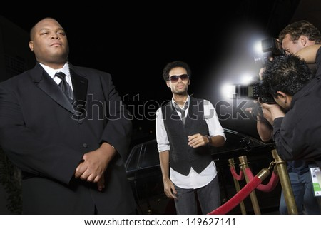 Male celebrity being photographed at media event - stock photo