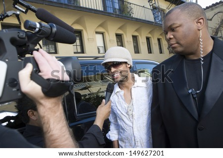 Male celebrity with bodyguard being interviewed by paparazzi - stock photo