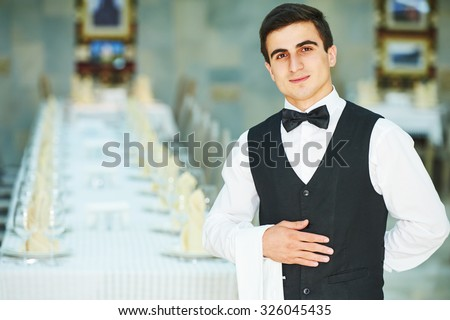 Male cheerful waiter in restaurant readu to service - stock photo