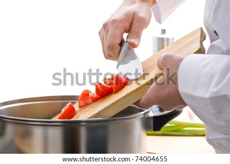 Male chef adding cut tomatoes to pot on stove