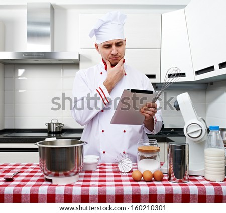 Male chef at kitchen with tablet pc getting ready to cook - stock photo