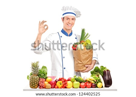 Male chef holding a bag with healthy ingridients behing a table full of various vegetables and fruits - stock photo