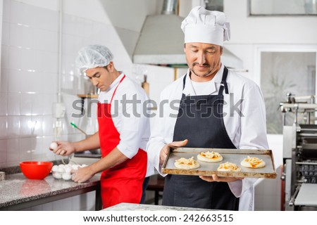 Male chef holding small pizzas on tray at counter with colleague in background at commercial kitchen - stock photo