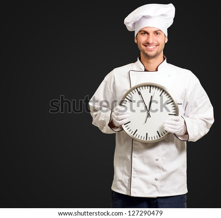 Male Chef Holding Wall Clock Isolated On Black Background - stock photo