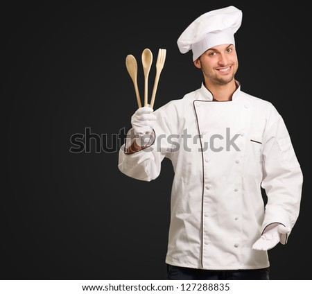 Male Chef Holding Wooden  Spoons Gesturing On Black Background - stock photo