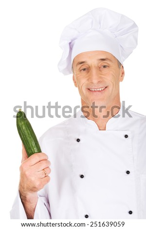 Male chef in uniform holding a cucumber - stock photo