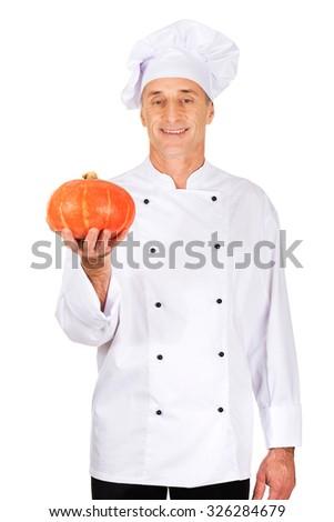 Male chef in uniform holding a pumpkin - stock photo