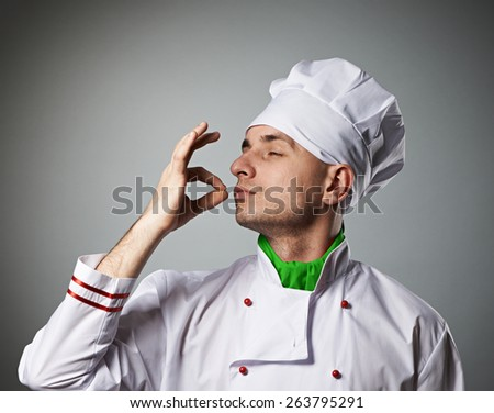 Male chef kissing fingers against grey background - stock photo