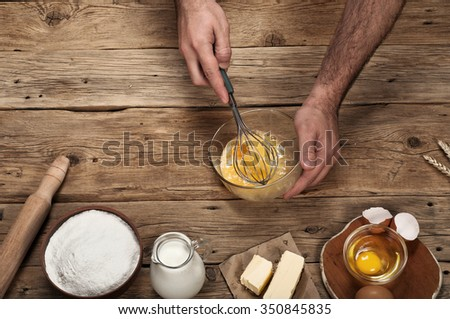 Male chef prepares on rustic kitchen. Ingredients for bakery products. Top view. Free space for text. Copy space - stock photo