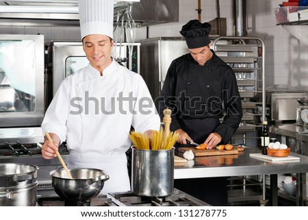 Male chef preparing food with colleague chopping carrot in industrial kitchen