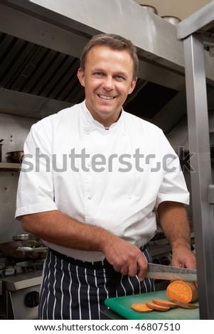 Male Chef Preparing Vegetables In Restaurant Kitchen - stock photo