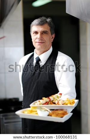 male chef presenting food meal in kitchen - stock photo