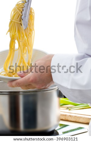 Male chef putting spaghetti from pot onto plate - stock photo