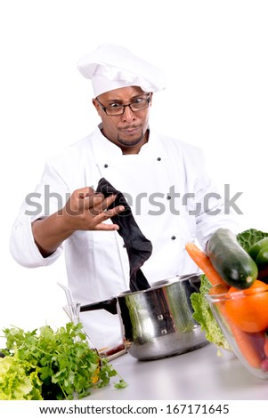 Male chef removing a dirty sock from frying pan - stock photo