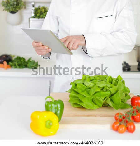 Male chef searching for recipe online with tablet pc