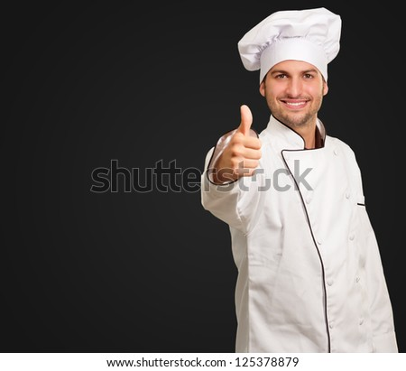 Male Chef Showing Thumbs Up Sign On Black Background - stock photo