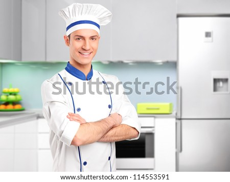 Male chef standing in a kitchen - stock photo