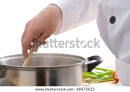 Male chef stirring meal in pot on stove