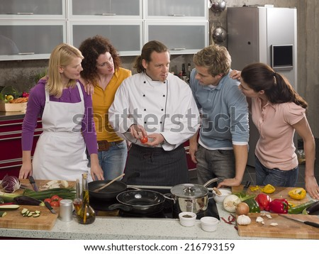 Male Chef teaching four students in the kitchen - stock photo