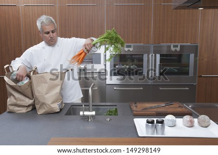 Male chef unpacking carrots from paper bags in commercial kitchen - stock photo