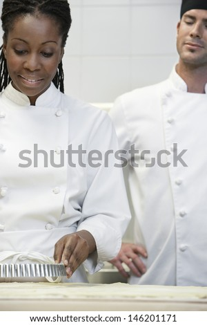 Male chef watching female colleague prepare food in the kitchen - stock photo