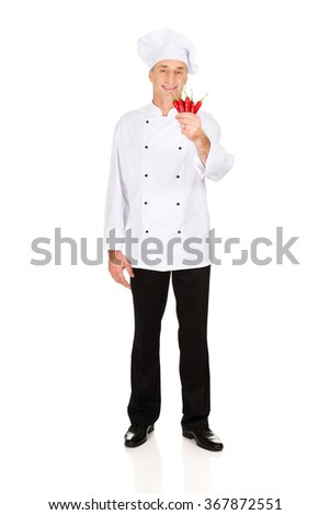 Male chef with chilli peppers - stock photo