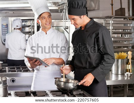 Male chef with digital tablet assisting colleague in preparing food at kitchen - stock photo