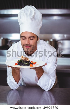 Male chef with eyes closed smelling food in commercial kitchen - stock photo