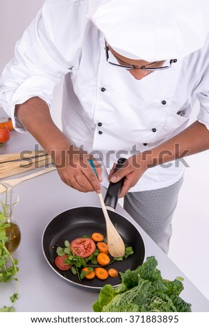 Male chef with fruits and vegetables cooking - stock photo
