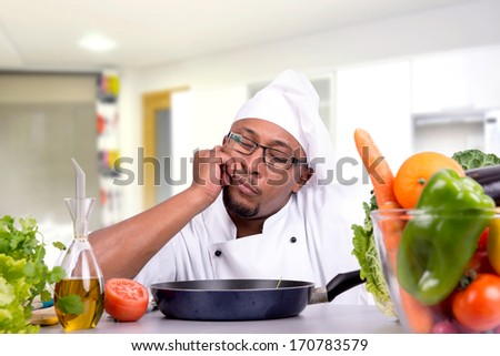 Male chef with fruits and vegetables in the kitchen thinking - stock photo