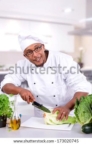 Male chef with fruits and vegetables on table - stock photo