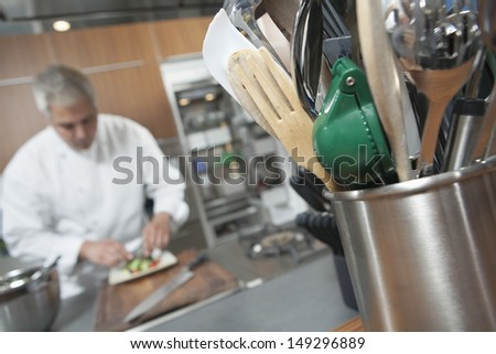 Male chef working with focus on utensil holder in foreground - stock photo