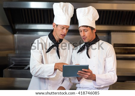 Male chefs holding clipboard while standing in commercial kitchen - stock photo