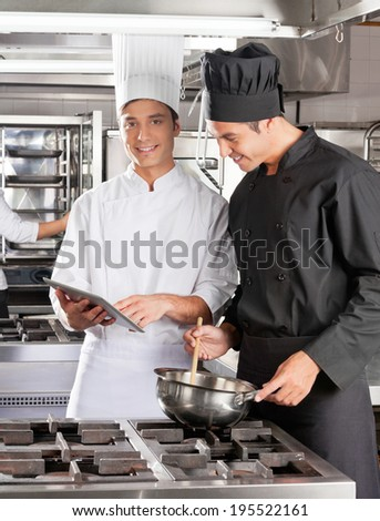 Male chefs with digital computer cooking food in commercial kitchen