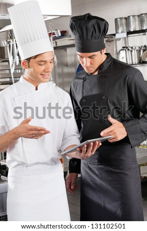 Male chefs with digital tablet discussing in restaurant kitchen - stock photo