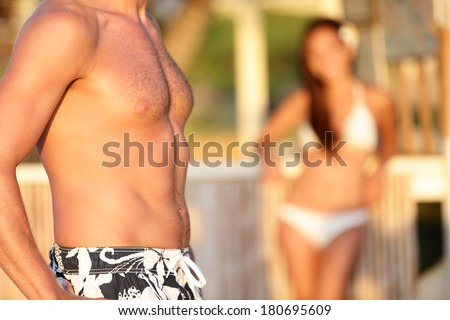 Male chest - woman looking at man torso on beach. Close up of handsome male torso. - stock photo