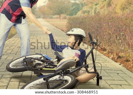 Male child crying after crashing with his bike and helped by his dad on the road - stock photo