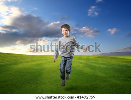 male child jumping in a grass field - stock photo