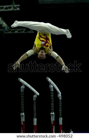 Male Chinese gymnast on parallel bars leaping into the air with a black background - stock photo