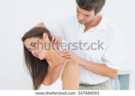 Male chiropractor massaging a young woman's neck in the medical office - stock photo